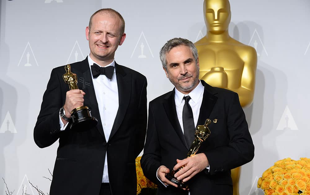 Alfonso Cuaron and Mark Sanger pose in the press room with the award for best film editing for 'Gravity' during the Oscars at the Dolby Theatre, in Los Angeles.