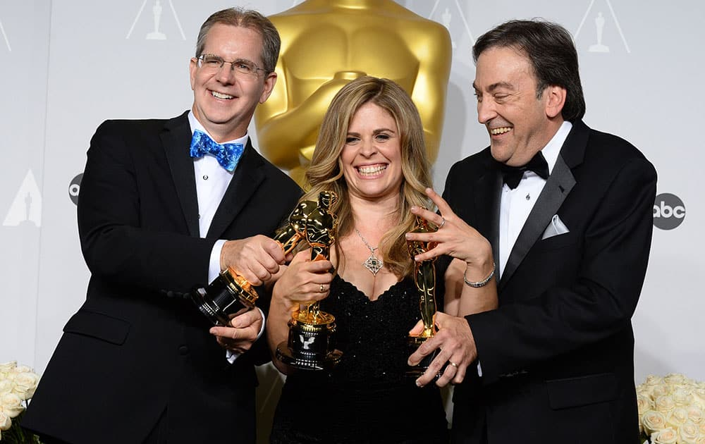 Chris Buck, Jennifer Lee and Peter Del Vecho pose in the press room with the award for Best animated feature film of the year for 'Frozen' during the Oscars at the Dolby Theatre.