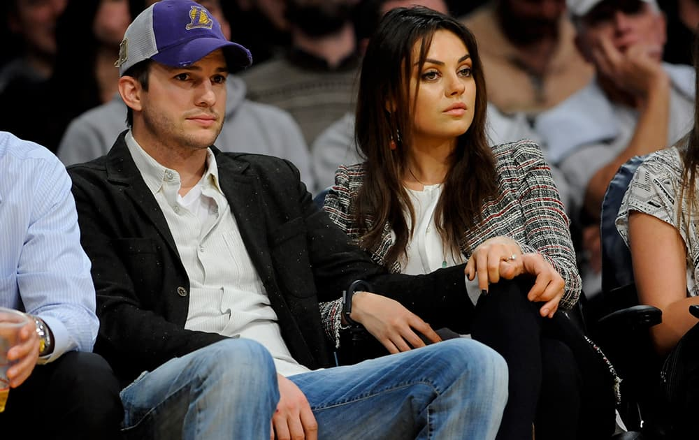 The newly engaged actors Ashton Kutcher and Mila Kunis attend an NBA basketball game between theNew Orleans Pelicans and Los Angeles Lakers in Los Angeles.