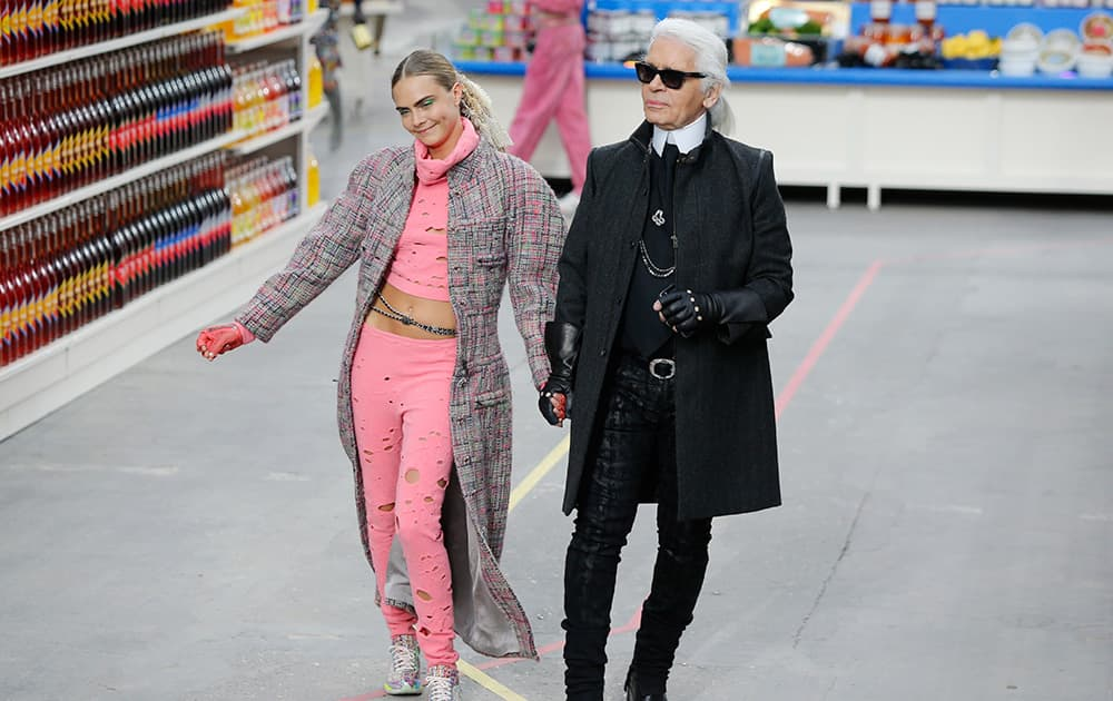 Model Cara Delevingne clowns next to German fashion designer Karl Lagerfeld after the presentation of Chanel's ready to wear fall/winter 2014-2015 fashion collection presented in Paris.