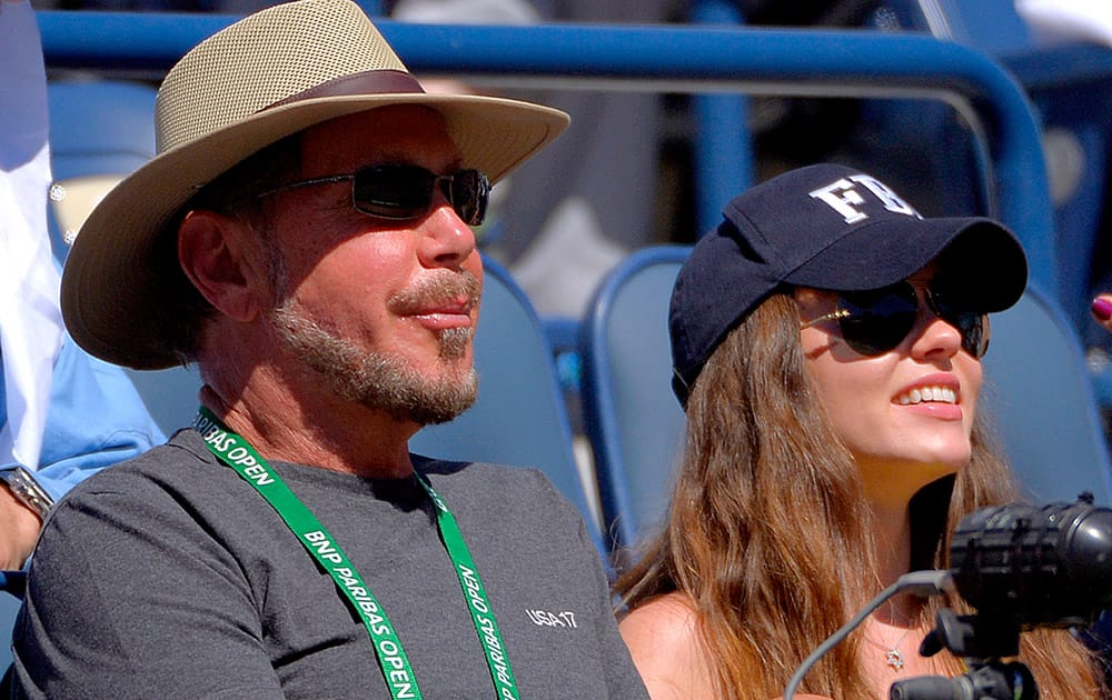 Oracle CEO Larry Ellison and his girlfriend, Ukranian actress Nikita Kahn, watch Roger Federer, of Switzerland, and Dmitry Tursunov, of Russia, competet during a third round match at the BNP Paribas Open tennis tournament.