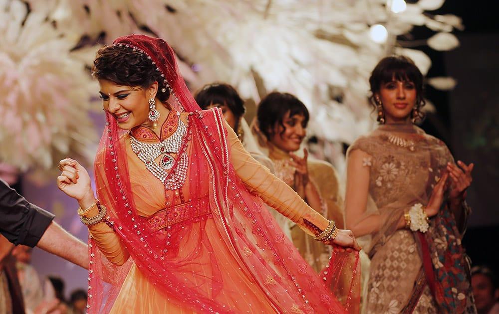 Bollywood actress Jacqueline Fernandez dances on the ramp to showcase a creation by Tarun Tahiliani during the Lakme Fashion Week in Mumbai.