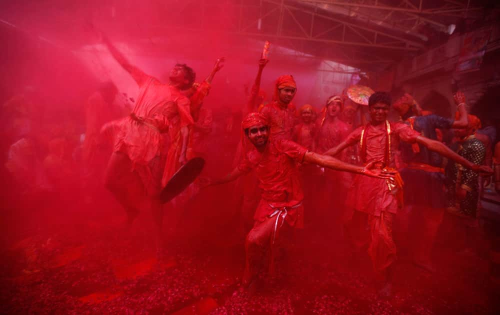 Men from the village of Nandgaon throw colored powder on others as they play holi at the Ladali or Radha temple, before the procession for the Lathmar Holi festival, the legendary hometown of Radha, consort of Hindu God Krishna, in Barsana.