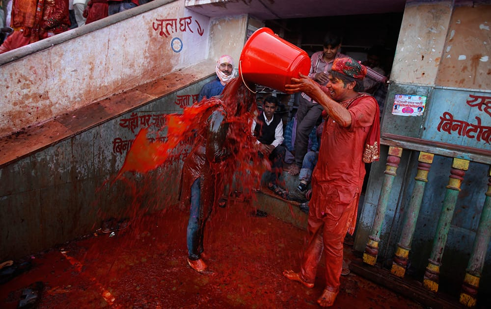 A Hindu man pours a bucket of colored water on a woman outside the Ladali or Radha temple before the procession for the Lathmar Holi festival, the legendary hometown of Radha, consort of Hindu God Krishna, in Barsana.