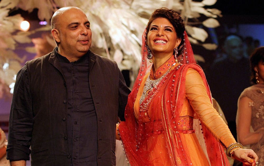 Jacqueline Fernandez alongwith designer Tarun Tahiliani walks the ramp displaying his collection on the first day of the Lakme Fashion Week 2014 in Mumbai.