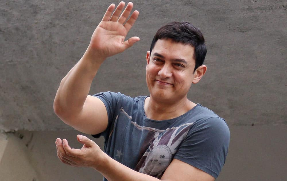 Amir Khan waves at his fans gathered outside his house to wish the actor on his 49th birthday in Mumbai.
