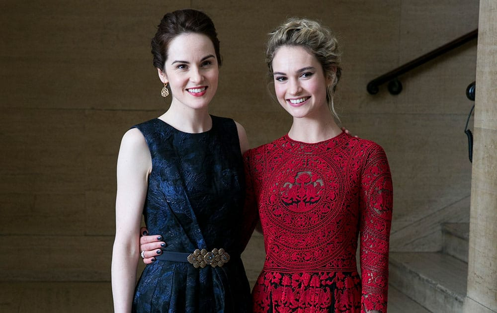British Actresses Michelle Dockery and Lily James pose for photographers as they arrive for the Changing Faces Gala Dinner, in London.
