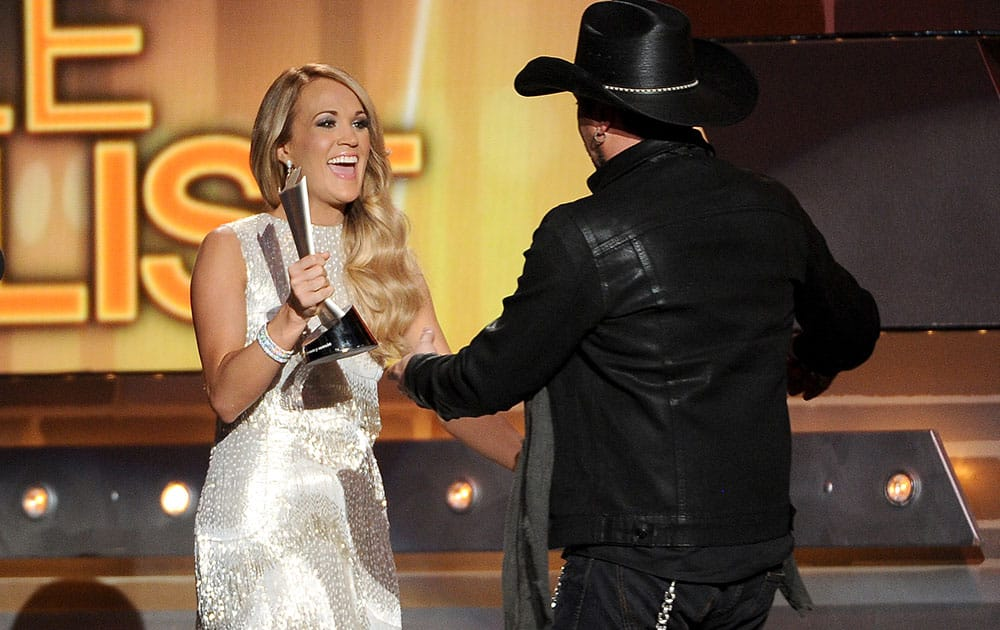 Carrie Underwood presents the award for male vocalist of the year to Jason Aldean at the 49th annual Academy of Country Music Awards at the MGM Grand Garden Arena in Las Vegas.
