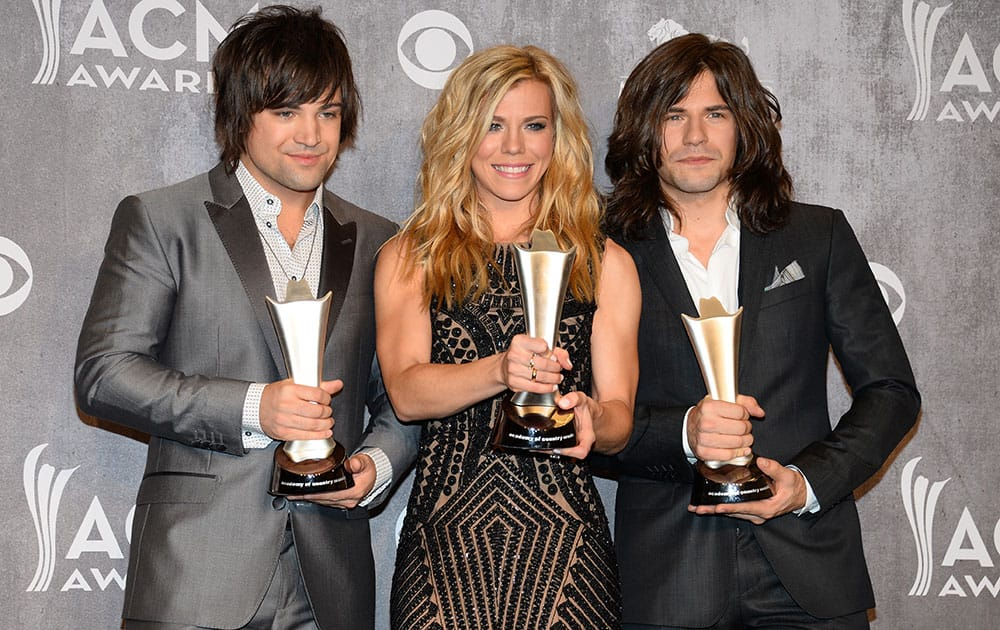 Dave Haywood, and from left, Hillary Scott and Charles Kelley, of the musical group The Band Perry, pose in the press room with the award for vocal group of the year at the 49th annual Academy of Country Music Awards at the MGM Grand Garden Arena in Las Vegas.