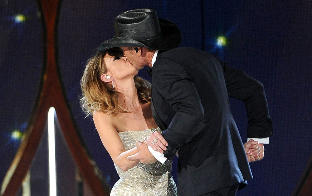 Faith Hill, left, and Tim McGraw kiss on stage at the 49th annual Academy of Country Music Awards at the MGM Grand Garden Arena in Las Vegas.