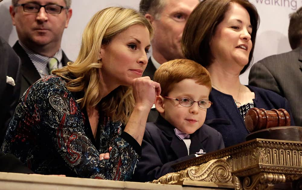Supermodel Niki Taylor and March of Dimes 2014 National Ambassador Aidan Lamothe watch floor activity from the podium before ringing the New York Stock Exchange closing bell.