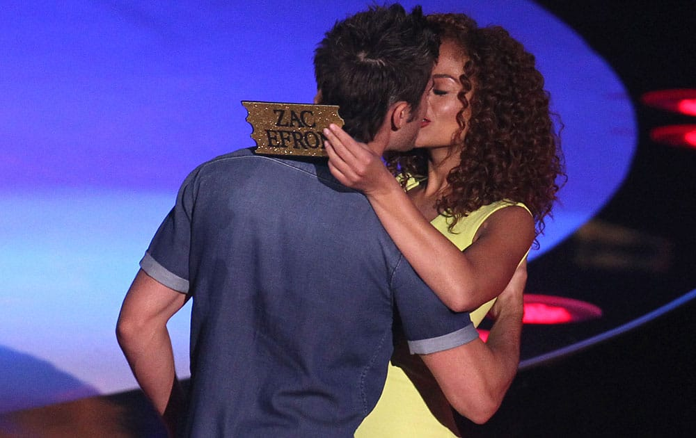 Zac Efron, left, kisses a contestant on stage at the MTV Movie Awards at Nokia Theatre in Los Angeles.