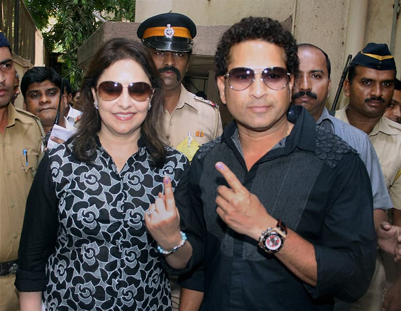 Master Blaster Sachin Tendulkar with wife Anjali Tendulkar display their inked finger after casting their vote in the Lok Sabha Elections 2014 in Mumbai.