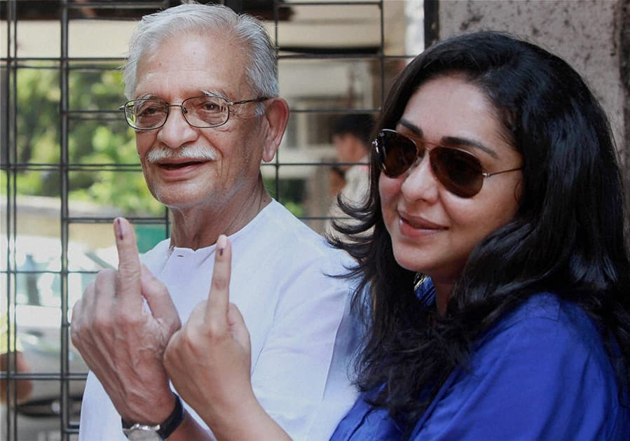 Poet Gulzar and his daughter display their inked fingers after casting their votes in Mumbai.