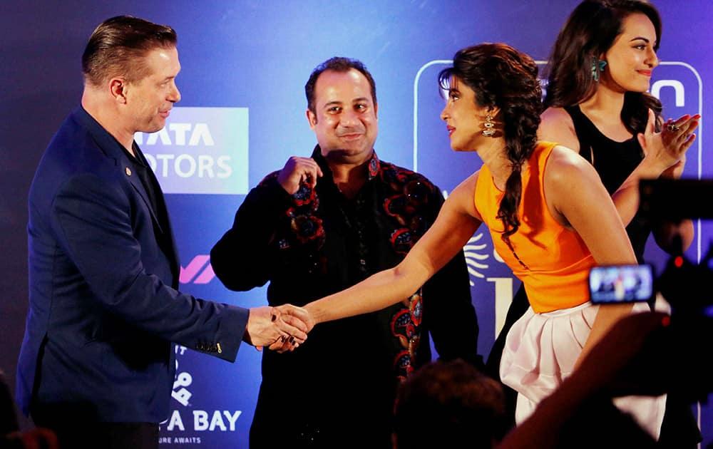 Priyanka Chopra shakes hands Hollywood star Stephen Andrew Baldwin as Pakistani Sufi singer Ustad Rahat Fateh Ali Khan looks on at International Indian Film Academy (IIFA) function in Florida, US.