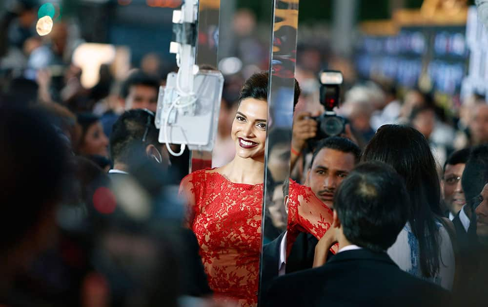 Deepika Padukone walks the green carpet as she arrives for the 15th annual International Indian Film Awards in Tampa, Fla.