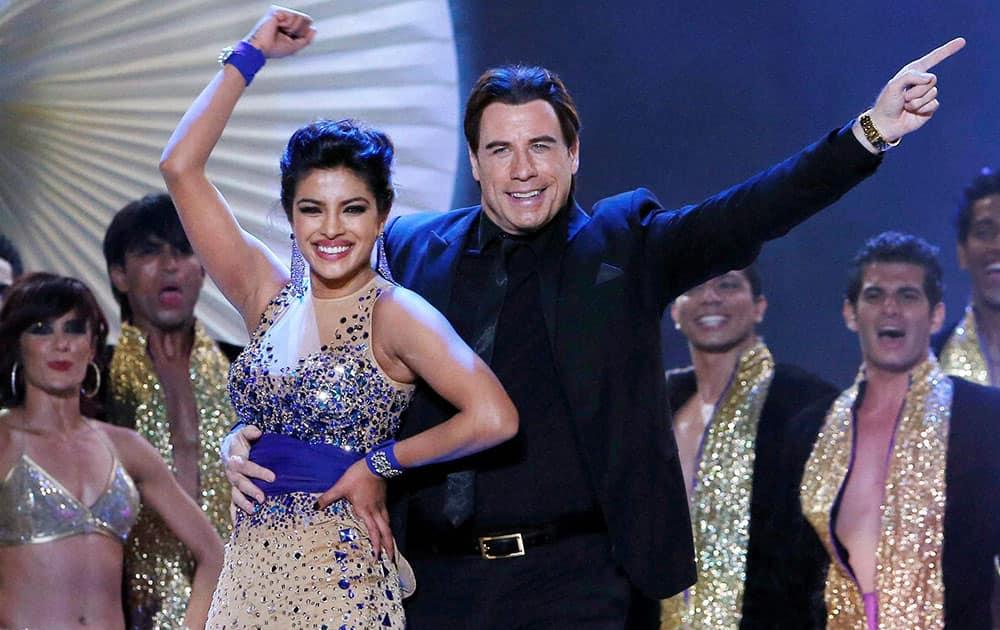Hollywood star John Travolta dances with Bollywood actress Priyanka Chopra at the 15th IIFA Awards in Tampa.