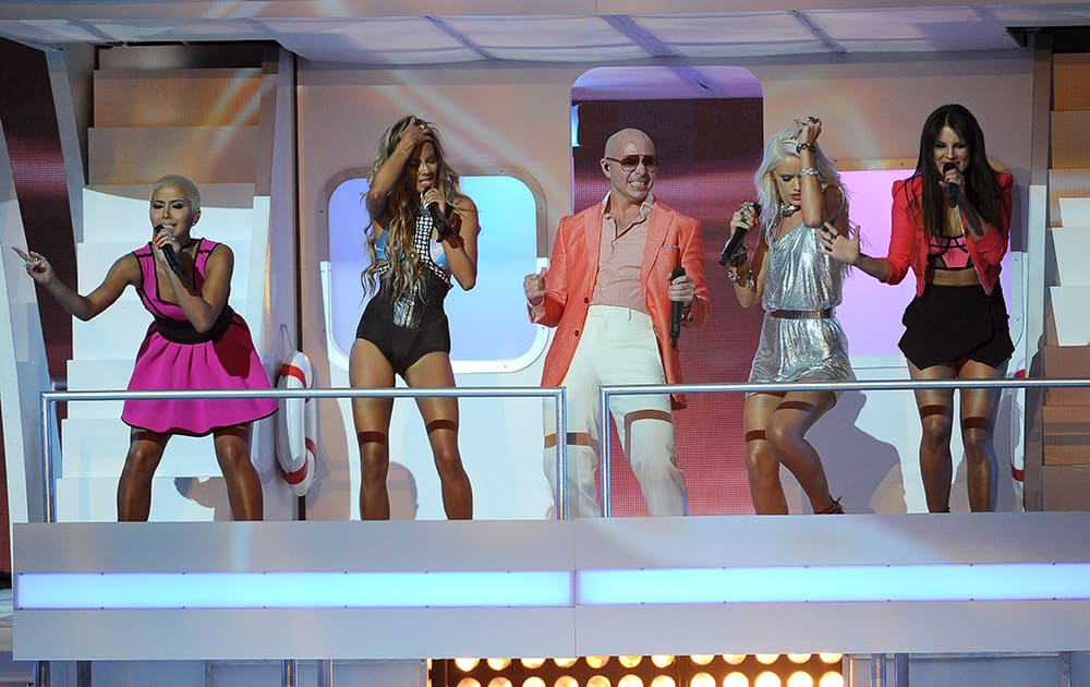 Pitbull, center, and from left, Paula Van Oppen, Emmalyn Estrada, Lauren Bennett and Natasha Slayton, of G.R.L., perform at the iHeartRadio Music Awards at the Shrine Auditorium in Los Angeles.