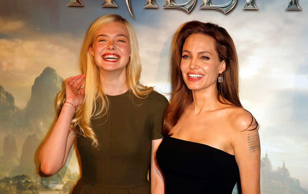 Actresses Angelina Jolie and Elle Fanning pose during a photocall for the film `Maleficent` (Malefique) in Paris.