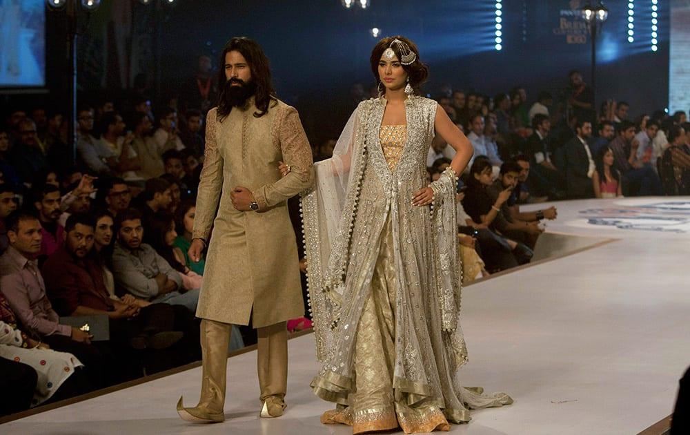 Models present creation by designer Sana Abbas during a Bridal Couture Fashion show in Karachi, Pakistan.
