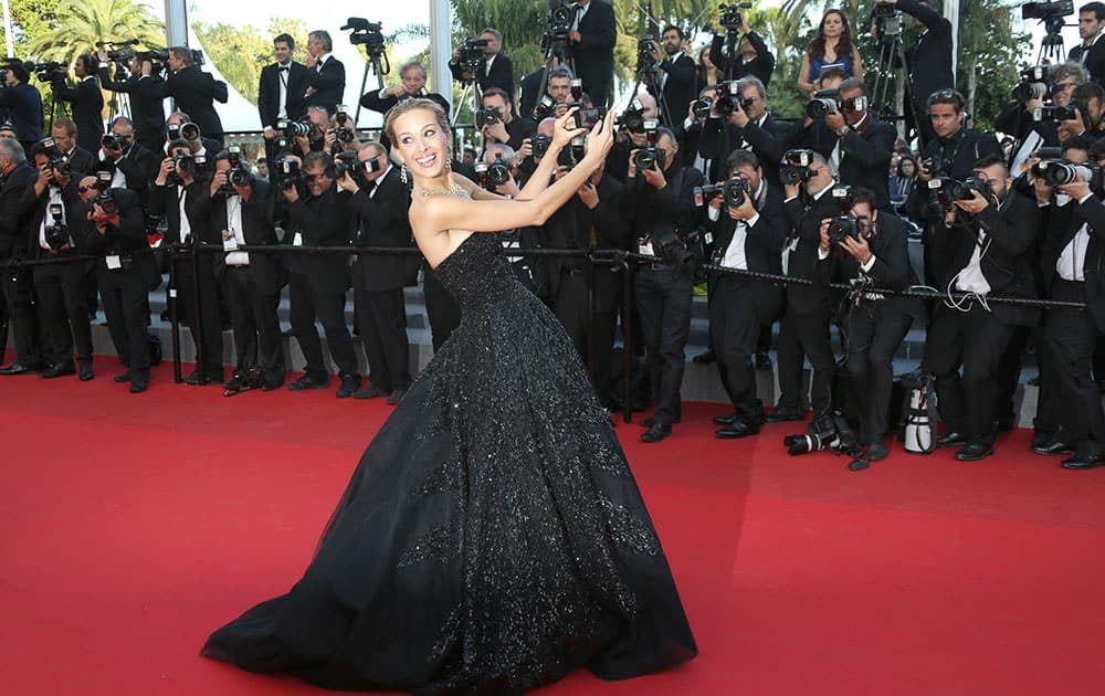 Model Petra Nemcova takes a photo with a phone on the red carpet for the screening of Two Days, One Night (Deux jours, une nuit) at the 67th international film festival, Cannes, southern France.