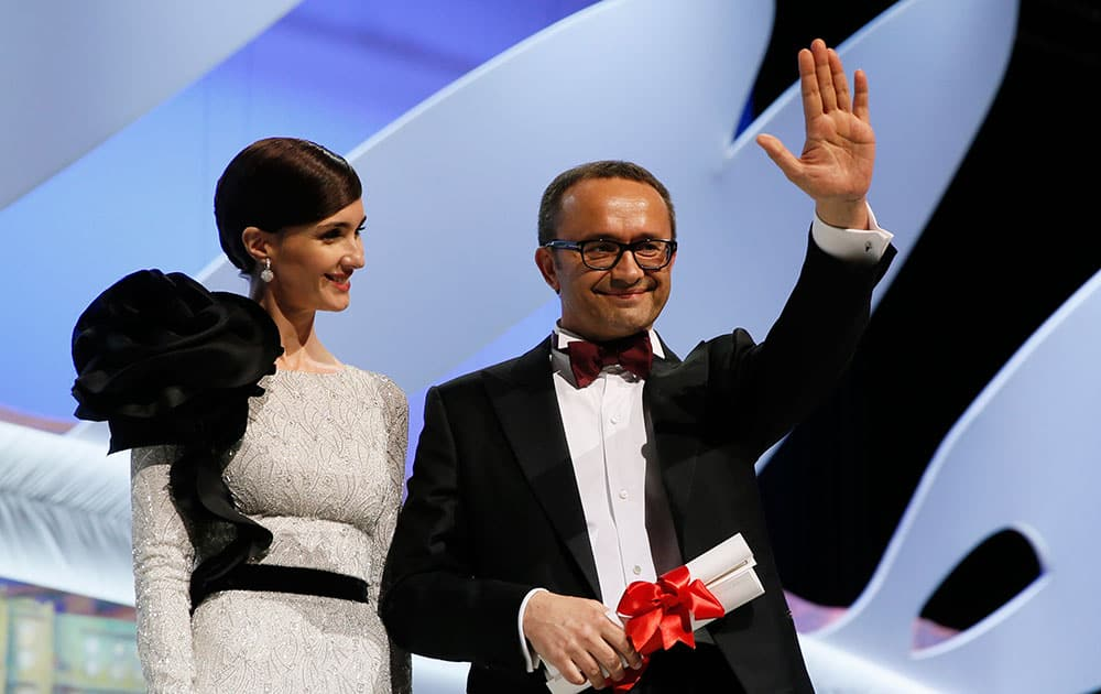 Director Andrey Zvyagintsev, right, acknowledges the audience after winning the Best Screenplay award for the film Leviathan, which was presented to him by actress Paz Vega during the awards ceremony for the 67th international film festival, Cannes.
