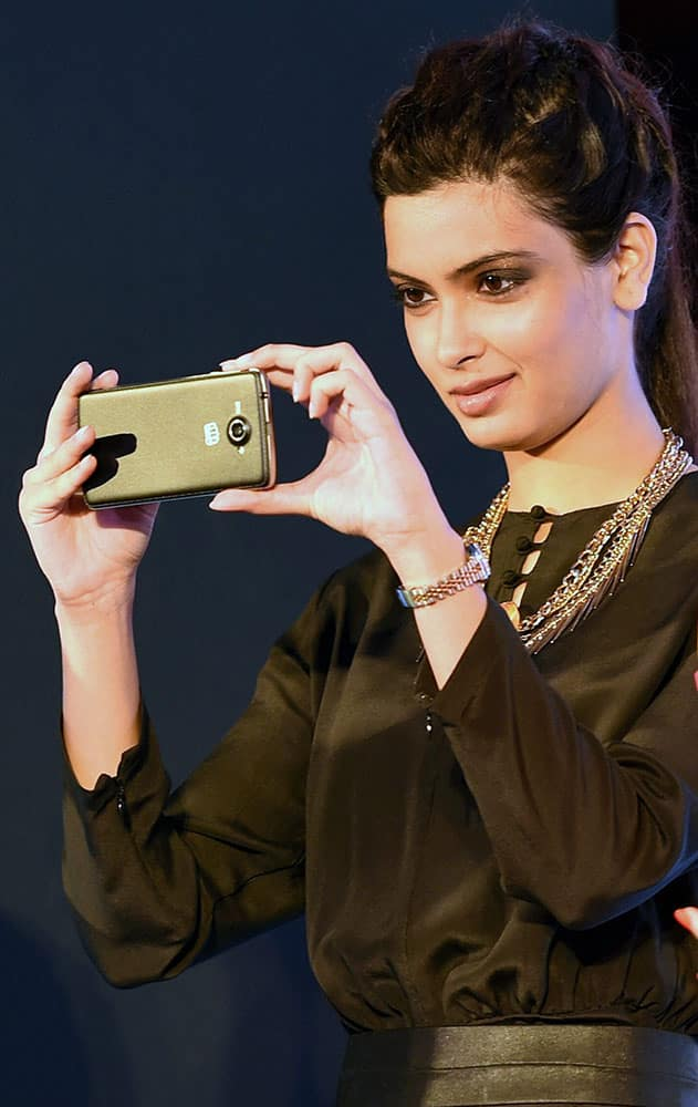 Diana Penty clicking pictures from the Micromax Canvas Win smartphone during its launch in New Delhi.
