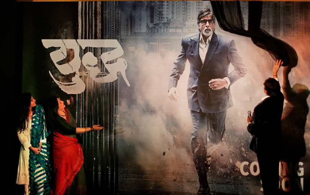 Amitabh Bachchan, unveils the poster of his upcoming television fiction series 'Yudh' as co-actors, Aahana Kumra and Sarika, watch during its promotion in New Delhi.
