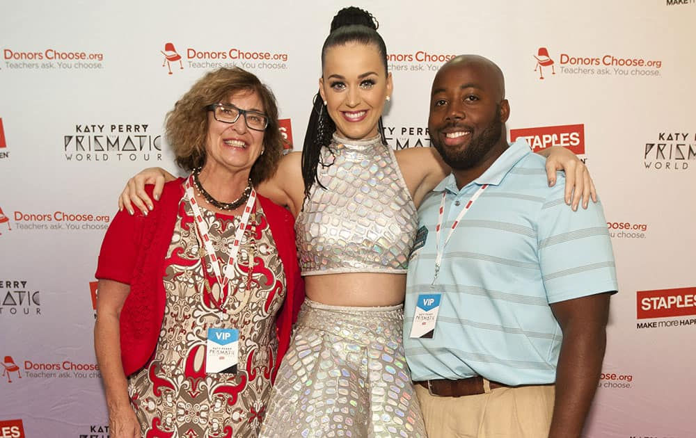 Global pop star Katy Perry with local teachers Pauline Weisz, left, and Matthew Hall, right, backstage at the Philips Arena during her Prismatic World Tour performance in Atlanta, GA.