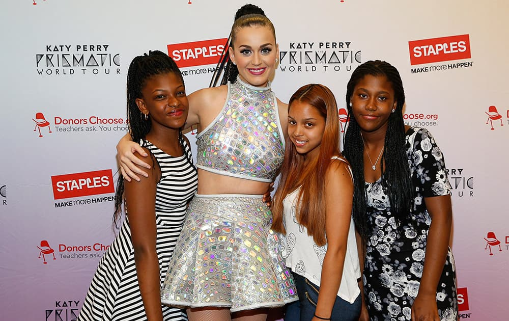 Global pop star Katy Perry, center, meets with local students, left to right, Jahnay Bryan, student Krysten Martinez, and Dorothy Toure backstage at Madison Square Garden during her Prismatic World Tour performance in New York.