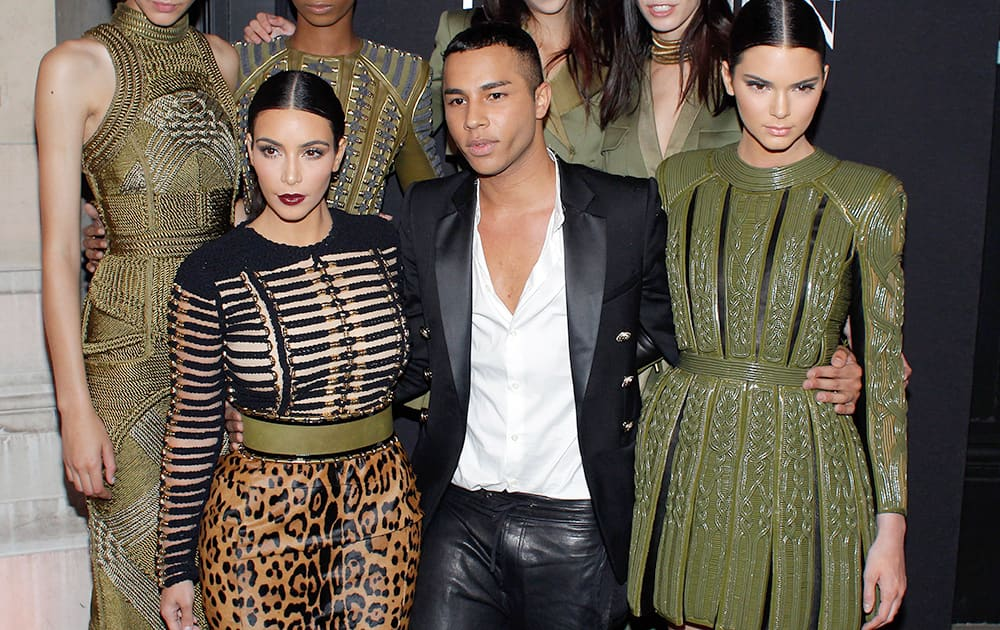 Fashion designer Olivier Rousteing, center, Kim Kardashian, left, and her sister Kendall Jenner pose prior to attend the Vogue party, in Paris.