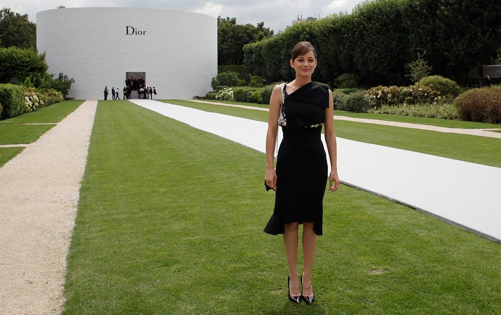 French actress Marion Cotillard poses for photographers as she attends Dior's Fall-Winter 2014-2015 Haute Couture fashion collection, in Paris.
