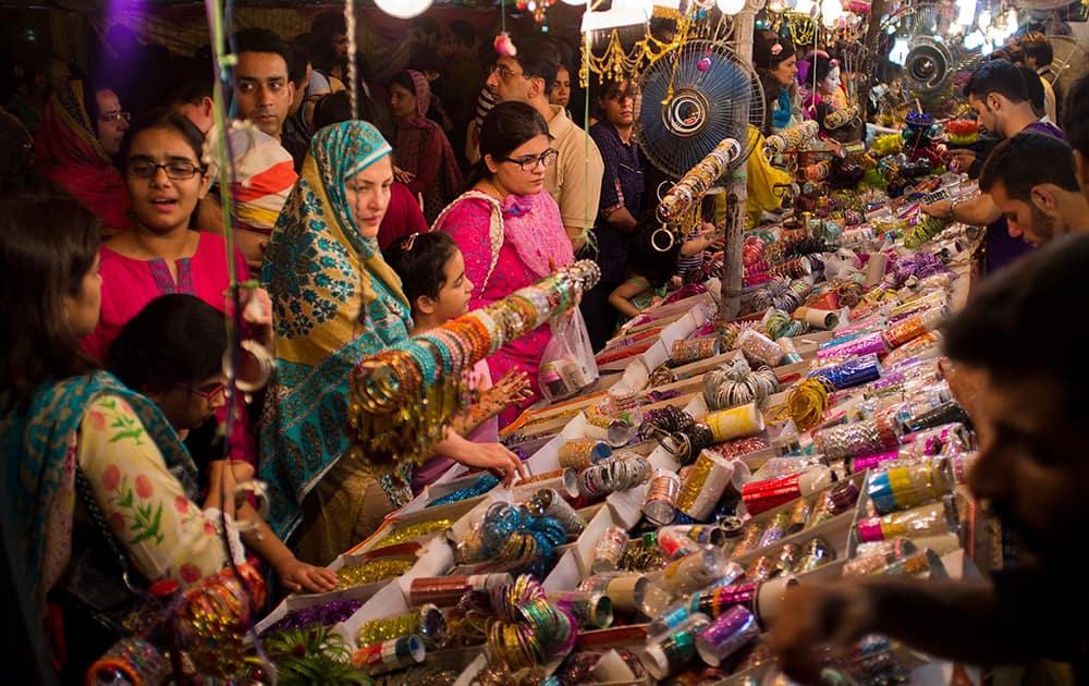 Pakistani customers buy bangles ahead of the Muslim holiday of Eid al-Fitr in Islamabad.