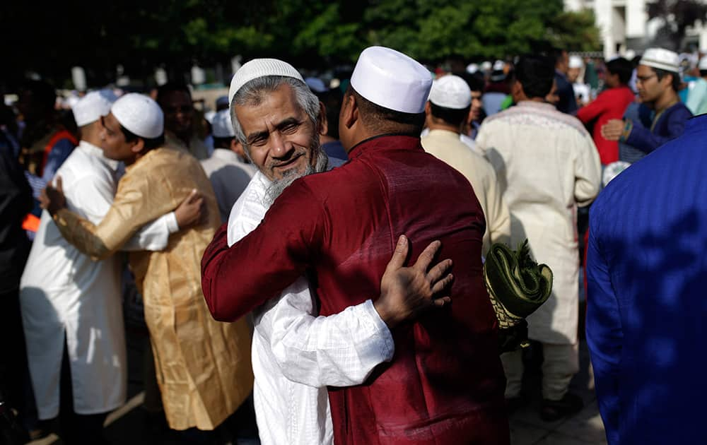 Muslim worshippers greet each others after the dawn prayer during the first day of the Eid al-Fitr, that marks the end of the holy fasting month of Ramadan, at Lisbon`s Martim Moniz square.