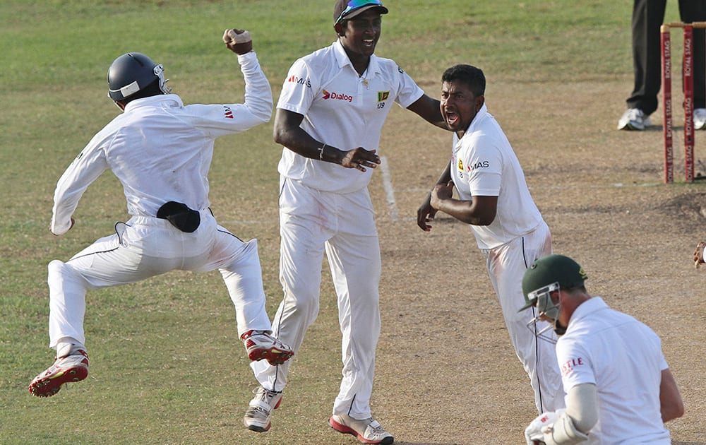 Sri Lankan bowler Rangana Herath celebrates with his teammates the dismissal of South African batsman Dale Steyn during the fifth day of the second test cricket match between South Africa and Sri Lanka in Colombo, Sri Lanka.