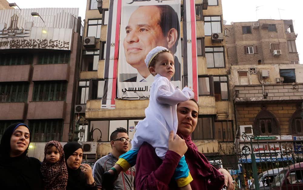 An Egyptian family walks under a giant banner supporting Egyptian President Abdel Fattah el-Sissi as they celebrate Eid al-Fitr, marking the end of the Muslim holy fasting month of Ramadan, in Cairo, Egypt.