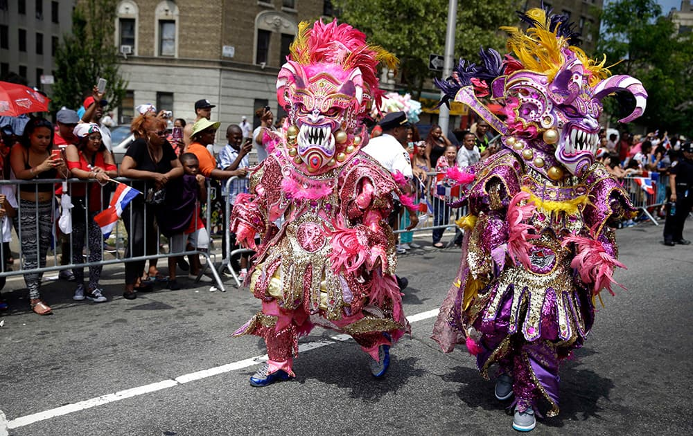 Men dressed in elaborate costumes march in the Dominican Day Parade in the Bronx borough of New York.