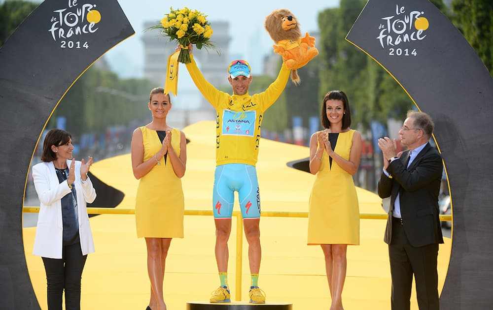 Race winner Vincenzo Nibali of Italy, wearing the overall leader`s yellow jersey, celebrates on the podium of the Tour de France in Paris, France.