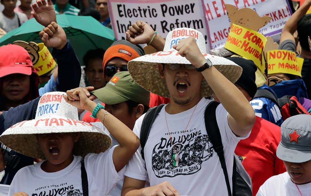 Protesters shout slogans as they march towards the residence of Philippine President Benigno Aquino III during a protest on the eve of Aquino`s State-of-the-Nation address at suburban Quezon city, northeast of Manila, Philippines.