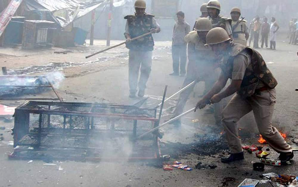Police men dousing the fire at a rack during violent clashes between two communities over a land dispute in Saharanpur.