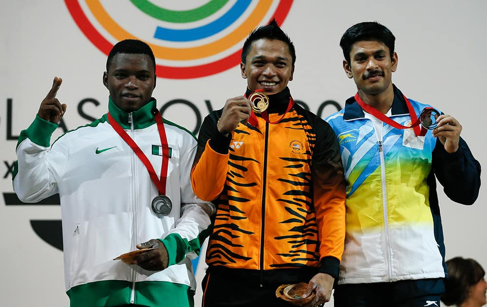 Gold medalist Mohd Hafifi Mansor of Malaysia, centre, with Yinka Ayenuwa of Nigeria, left, silver medal and Omkar Otari of India with the bronze medal pose for photographs after the medal ceremony for the men`s 69 kg weightlifting competition at the Commonwealth Games Glasgow 2014.