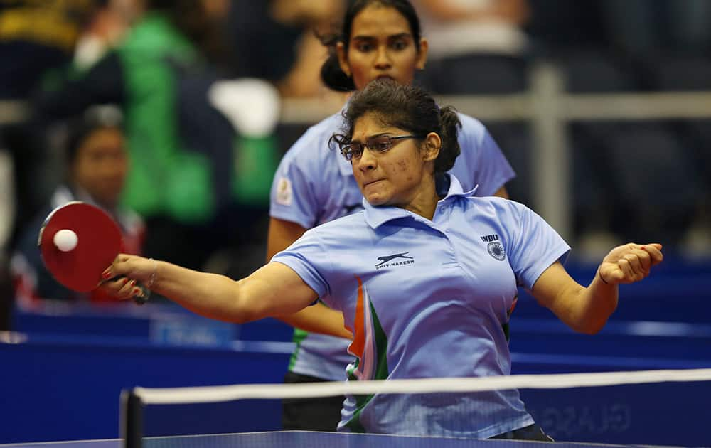India`s Madhurika Sushas Patkar and Shamini Kumaresan serve to Yang Sun and Karen Li during their women`s doubles table tennis quarterfinal match at the Scotstoun sports center in Glasgow, Scotland.