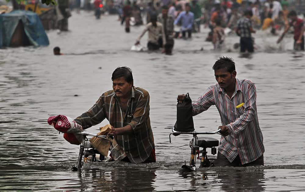 Indian men push their bicycles as they wade through a water- logged area after heavy monsoon rains in Ahmedabad.