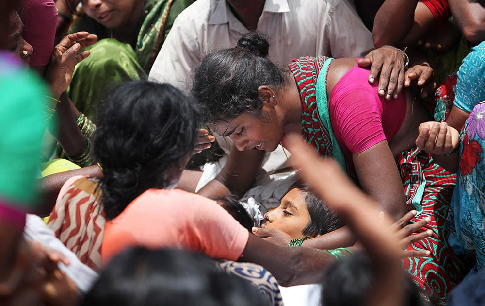 An unidentified woman cries by the body of a victim of an accident in Medak district in the southern Indian state of Telangana.