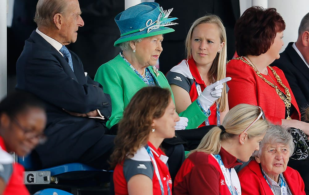 Britain`s Queen Elizabeth II , center, and Prince Philip, Duke of Edinburgh, left, sit to watch hockey at the Commonwealth Games 2014 in Glasgow, Scotland.