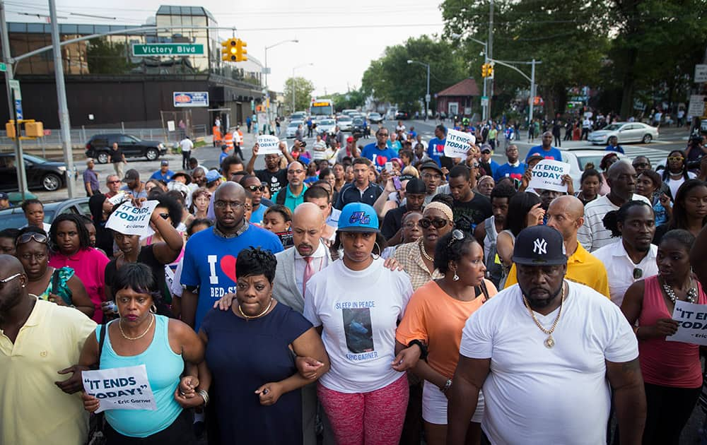 Ellisha Flagg, sister of Eric Garner, center, leads demonstrators on a march towards the 120th Precinct following a vigil demanding justice for her brother who died while being arrested by New York City police in New York.