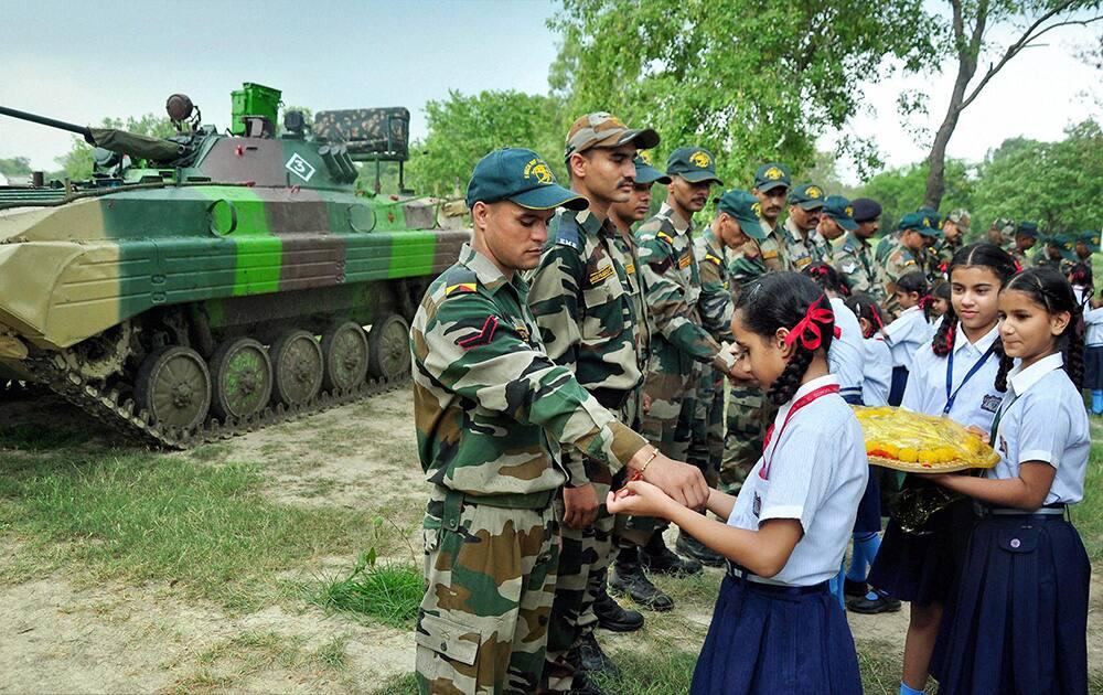 School girls tie rakhi on the wrists of Army soldiers on the eve of Raksha Bandhan festival in Patiala.