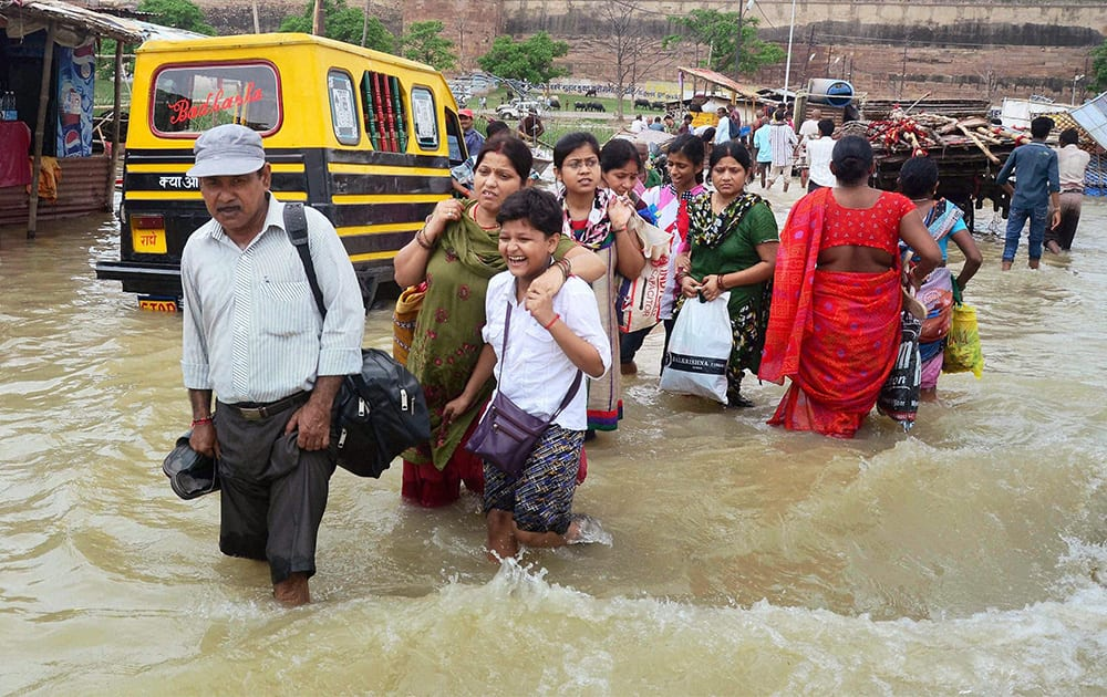People struggle to move across a flooded locality in Allahabad.