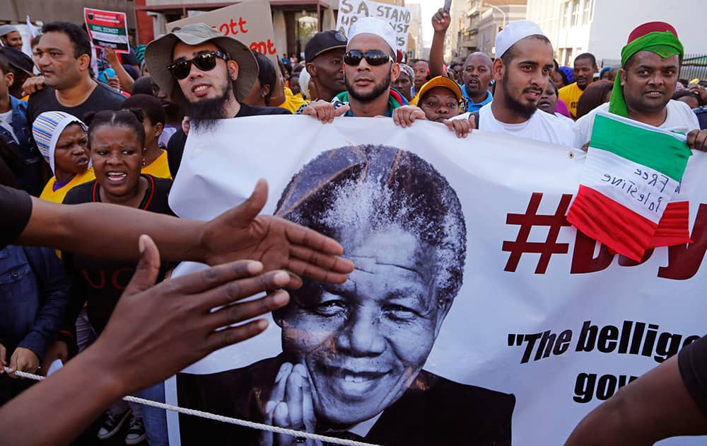A man`s hands, left, covers part a banner with the face of former South African President Nelson Mandela, as he takes part with other Palestinian supporters, in a rally against the Israeli occupation of the Palestinian territories in Cape Town, South Africa.