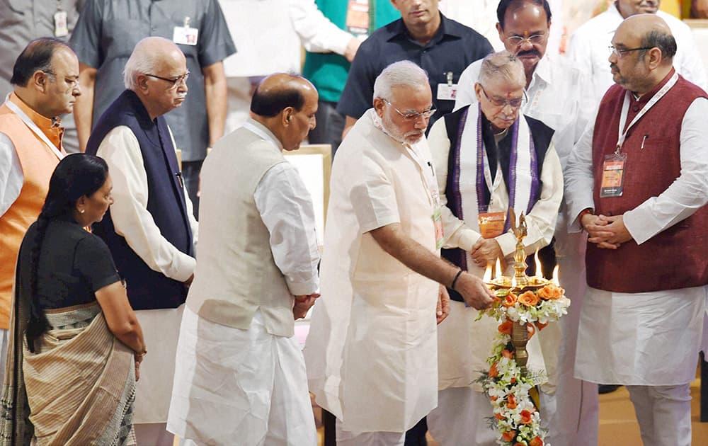 Prime Minister Narendra Modi lighting the lamp as BJP President Amit Shah and senior leaders LK Advani, M M Joshi, Rajnath Singh, M Venkaiah Naidu, Arun Jaitley and Gujarat CM Anandiben Patel look on during the party`s National Council meet in New Delhi.